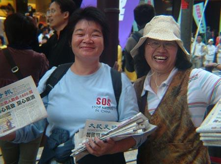На фото показані дві всміхнені співробітниці газети 'Велика Епоха', які тримають у руках спеціальні випуски, які присвячені виходу з КПК. В однієї зі співробітниць на футболці написано: 'Зупинити переслідування в Китаї'. 'Велика Епоха' в 2004 році опублік