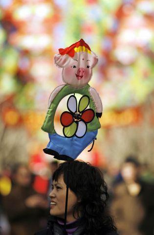 Китай. Пекин. Перед парком Дитань девушка несёт ветряки в форме свиньи. Фото: Peter Parks/AFP