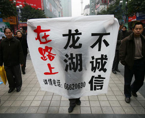 15 березня, 2007 р. Житель міста Чунцін, пров. Сичуань піднімає плакат протестуючи проти продажу земельних ділянок. China Photos/Getty Images