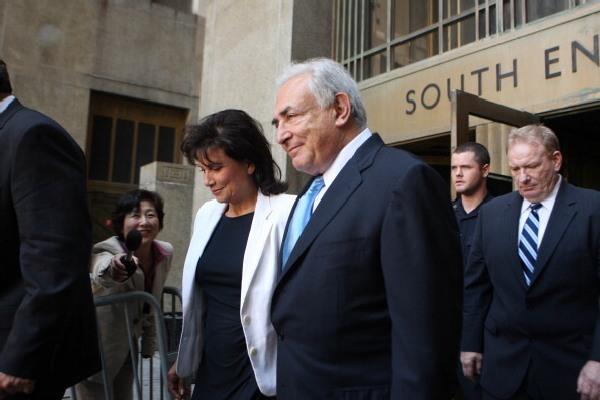 Экс-глава Международного валютного фонда Доминик Стросс-Кан и его жена Энн Синклер выходят из Верховного суда штата Нью-Йорк 1 июля 2011 года. Офис окружного прокурора Манхэттена согласился освободить Стросс-Кана без залога. Don Emmert / Getty Images