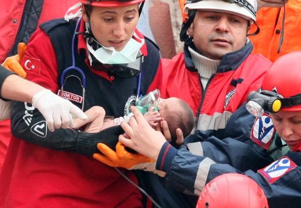 Турецкие спасатели держат двухнедельную девочку Азру Карадуман, которую достали из-под обломков обрушившегося здания в результате землетрясения. Эриш, 25 октября 2011 года. Фото: Adem Altan/Getty Images