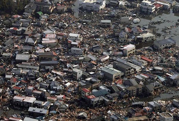 Разрушенные дома и мусор остаются на поле в городе Kesennuma, префектура Мияги 12 марта 2011 года. (JIJI PRESS/AFP/Getty Images)