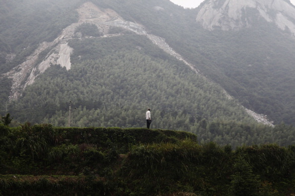 Местный житель у подножия горы, по которой спустился оползень. Провинция Хунань, Китай. Фото: STR/AFP/Getty Images