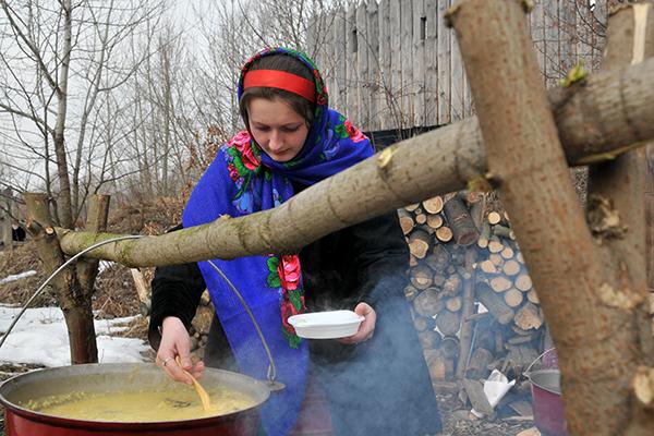 Дівчина кладе в тарілку козацьку кашу тетерю. Фото: Володимир Бородін / The Epoch Times Україна