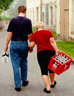 Лише б не надірватися. Чоловік тримає сумочку з кількома пляшками пива і допомагає йти жінці, яка несе ящик пива