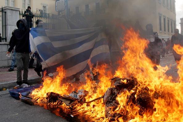 Демонстранти спалюють прапор Греції, тим самим нагадуючи про вбивство 15-річного Александроса Грігорополоса поліцейськими рік тому. Афіни, Греція. Фото: Bicanski / Getty Images