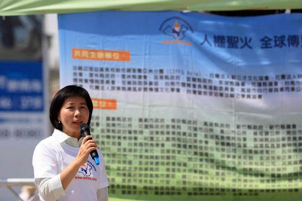 7 червня. Місто Каосюн (Тайвань). Представник місцевого уряду пані Хуан Чахуань виступає з промовою на мітингу. Фото з minghui.org