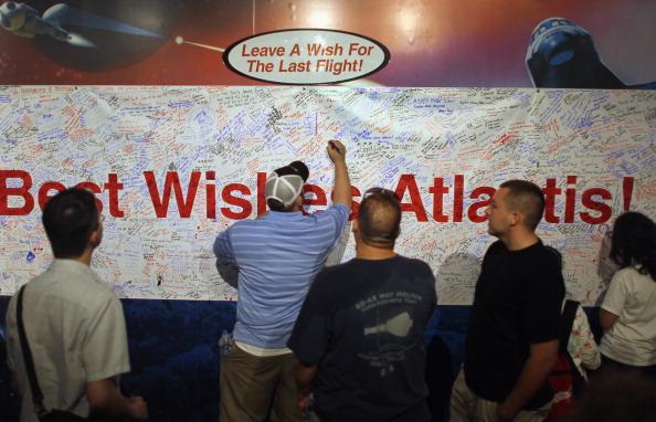 Відвідувачі пишуть побажання на постері в Космічному центрі ім. Кеннеді. Напис у центрі: «Найкращі побажання Атлантісу». Напис зверху: «Напиши побажання останньому польоту». Фото: Joe Raedle/Getty Images