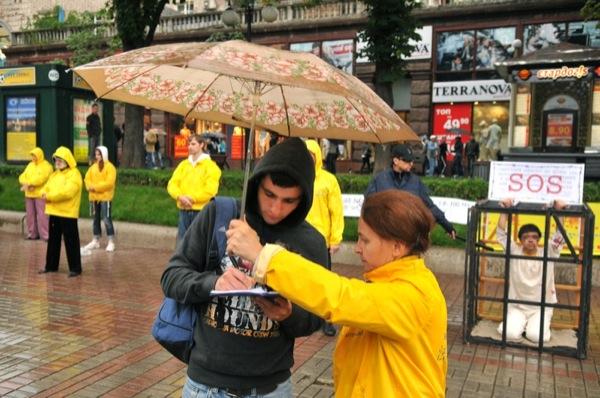 Учасниця акції послідовників Фалуньгун збирає підписи за звільнення однодумниці, яку катують у китайській в'язниці. Фото: Володимир Бородін/The Epoch Times Україна