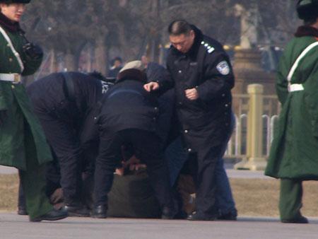 Поліція б'є чоловіка, притиснувши його до землі. Фото: Minghui Net