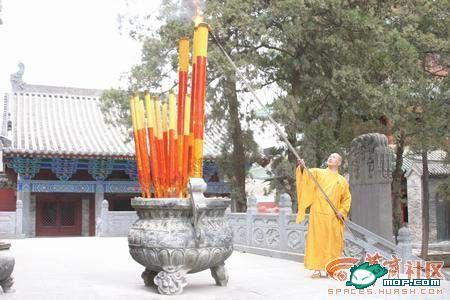 Чернець Шаолінь запалює величезну свічку з пахощами. Одна така свічка для туристів коштує 6000 юанів (857$), а найдорожча коштує 10 тисяч юанів (1428$). Фото: з сайту epochtimes.com
