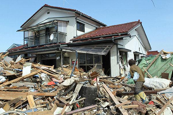 Женщина вернуась к своему разрушенному дому в городе Натори в префектуре Мияги 13 марта 2011. (JIJI PRESS/AFP/Getty Images)