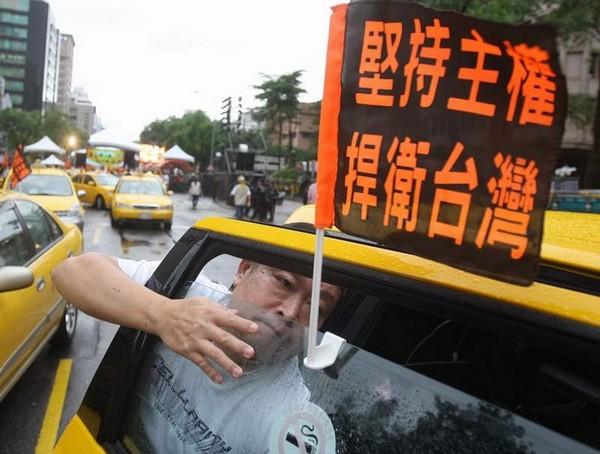 Водитель такси прикрепляет к машине флаг с надписью: «Отстоим суверенитет, защитим Тайвань». Фото: ЦАН