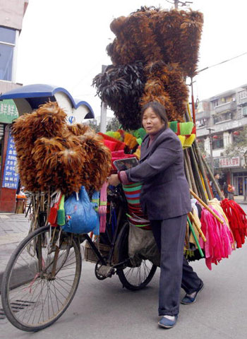 16 березня, 2007 р. Продавець м. Ченду продає мітли й віники на вулиці. Фото: Лю Цзінь/AFP/Getty