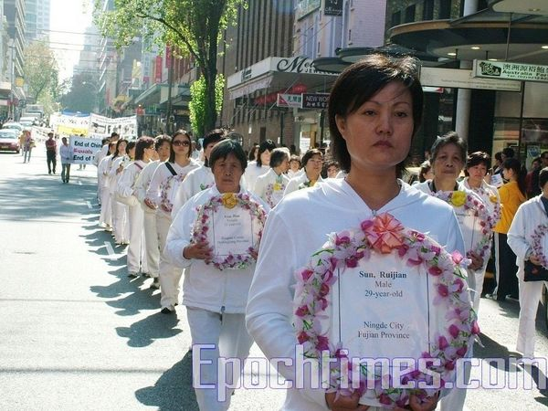 Колонна, несущая венки с именами последователей Фалуньгун, погибших от репрессий в Китае. Фото: Ло Я/The Epoch Times