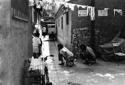 Женщины пристально следят за незнакомцем, приехавшим в их район. Город Пекин. 1999 год. Фото: Wu Qiang