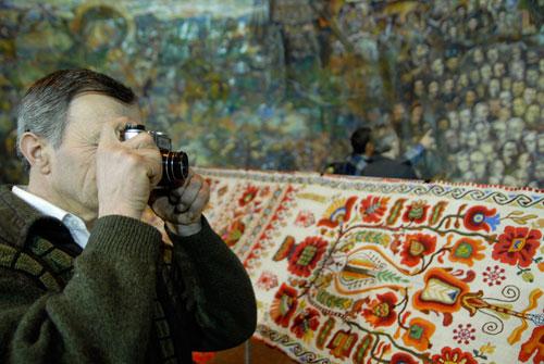 Чоловік фотографує картину Романа Бончука «Мегаісторія України» в Українському домі. Фото: Володимир Бородін/Велика Епоха