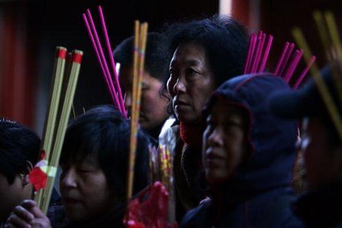 На китайский Новый год люди в храме Юнхэгун молятся и возжигают благовония. Фото: Guang Niu/Getty Images