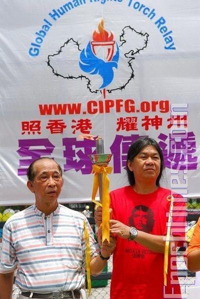 Сэ Тухуа и Лян Госюн держат Факел прав человека. 20 июля. Гонконг. Фото: Ли Мин/ The Epoch Times