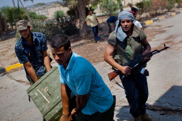 Ливийские повстанцы грабят оружие в бывшем военном городке Каддафи, Триполи, Ливия, 26 августа 2011 года. Фото: Daniel Berehulak / Getty Images