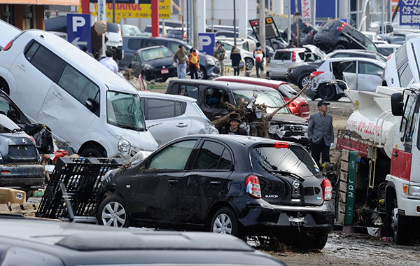 Люди идут по дороге, заваленной разбитыми автомобилями в Tagajo, префектуры Мияги, 13 марта 2011 г.. (TORU YAMANAKA/AFP/Getty Images)