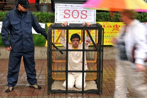 """Лі на мирній акції протесту проти тортур у Китаї. Інсценування методу тортур """"укладення в клітці"""", яка використовується у в'язницях Китаю в ході переслідування Фалуньгун. Інсценування проводиться з метою: привернути суспільну увагу до порушення прав людин"""