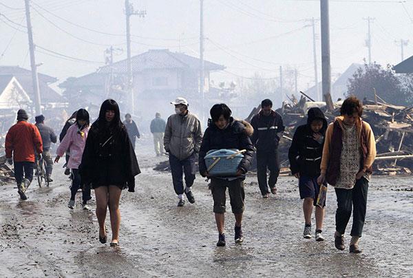 Люди идут по грязной дороге в эвакуационное убежище в городе Натори, префектуры Мияги 12 марта 2011 года. (STR/AFP/Getty Images)