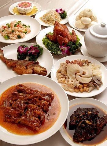 Комплексна страва. Салат з морепродуктів, смажена каракатиця із зеленою цибулею, смажений рак, смажене філе з цибулею, курка, тушкована з соєю, торт з червоної сої, китайські парові пиріжки з м'ясом. Фото з epochtimes.com