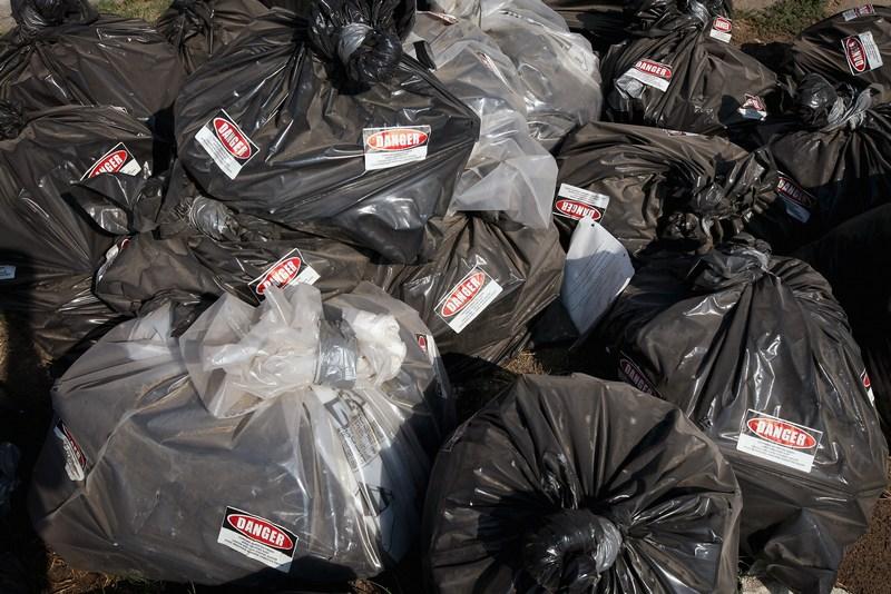 Мешки с кусками асбестового покрытия. Надпись на наклейке – «Опасно». Фото: Scott Olson/Getty Images