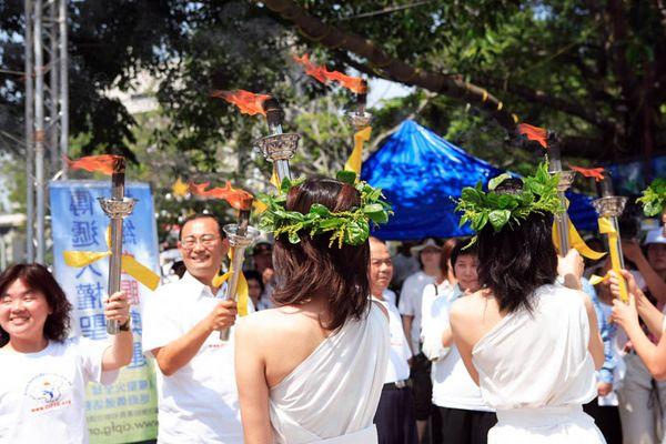 7 червня. Місто Каосюн (Тайвань). Дівчата в костюмах грецьких жриць передають факел чиновникам місцевої влади. Фото з minghui.org
