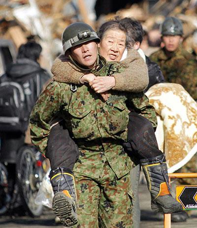 Солдат несет пожилую женщину на спине в городе Kesennuma в префектуре Мияги 12 марта 2011 года. (STR/AFP/Getty Images)