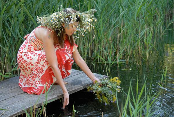 Девушка пускает в воду сплетенный венок. Фото: Владимир Бородин/The Epoch Times