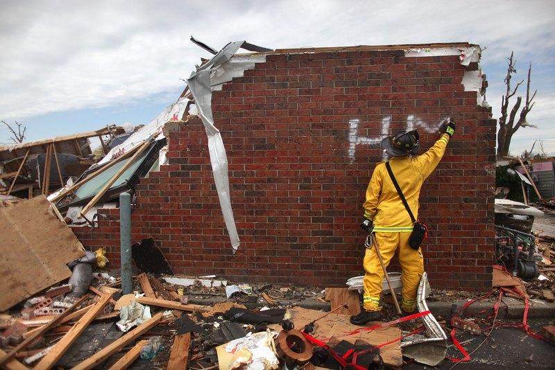 Пожарный пишет знак «HM» (heavy machinery – тяжелая техника) на стене разрушенного дома. Фото: Mario Tama/Getty Images