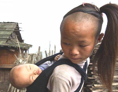 Девочка несущая маленького брата. Фото: Getty Images