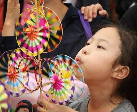 Гонгконг: девочка на рынке дует на бумажный ветряк. Фото: Mike Clarke/AFP