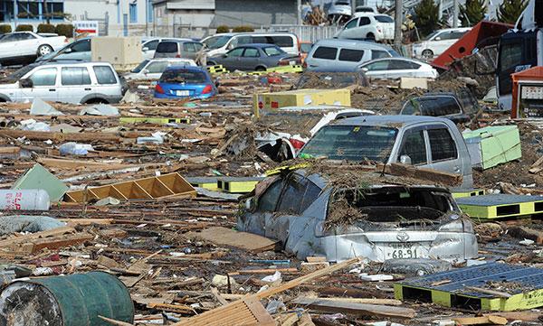 Автомобили утопленые в воде наполненной мусором после прошедшей цунами возле города Сэндай в префектуре Miyage 13 марта 2011. (MIKE CLARKE/AFP/Getty Images)