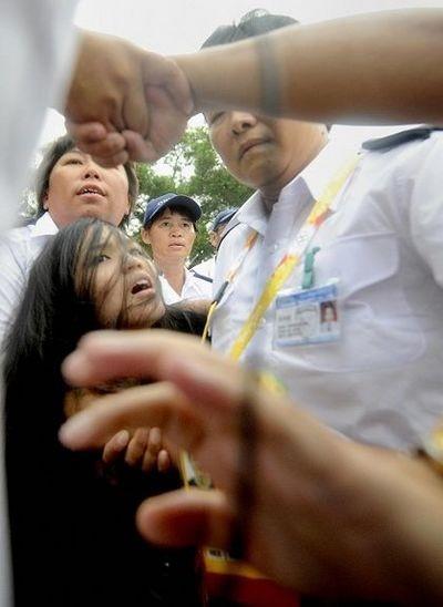 Полицейские арестовывают девушку, попытавшуюся во время олимпийских соревнований выразить протест против подавления китайской компартией тибетцев. 9 августа. Гонконг. Фото: DAVID HECKER/AFP/Getty Images