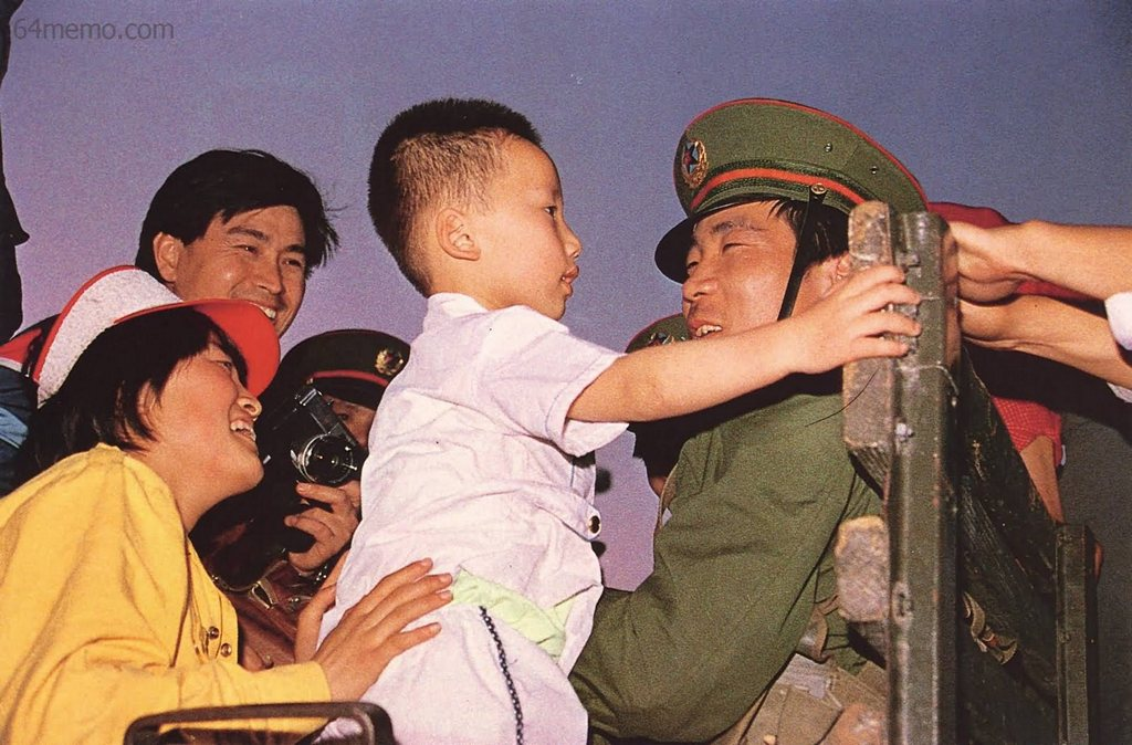 20 мая 1989 г. Началось военное положение. Женщина, участвующая в демонстрации протеста, знакомит солдат из оцепления со своим сыном. Фото: 64memo.com