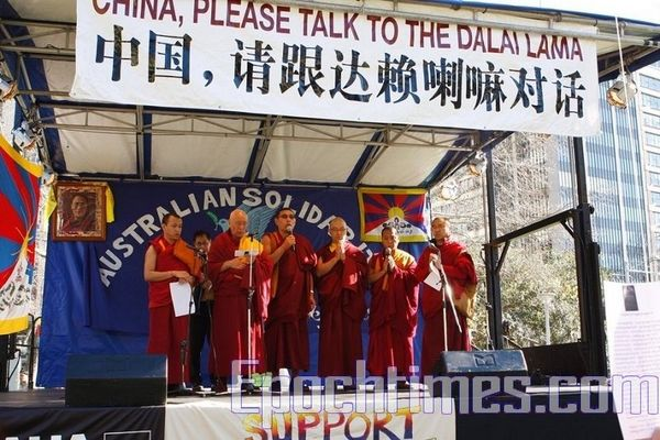 Тибетські лами хором читають мантри. На транспаранті написано: «Китай, будь ласка, проведи діалог із Далай-ламою». Фото: Сунь Ює/The Epoch Times