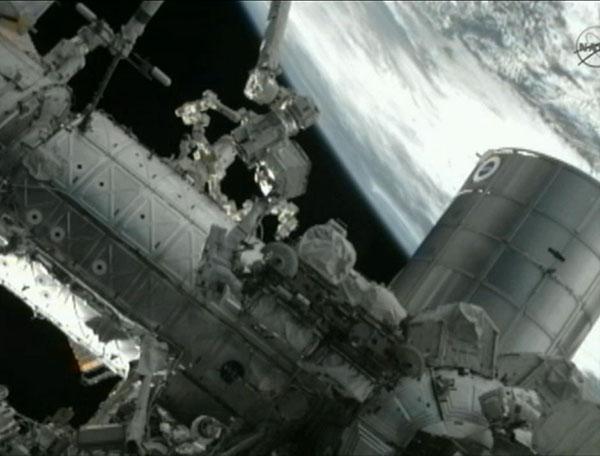 Астронавти Гаран і Фоссум встановлюють експериментальну систему автоматичної дозаправки супутників. Вгорі – дворукий робот «Декстре». Фото: nasa.gov