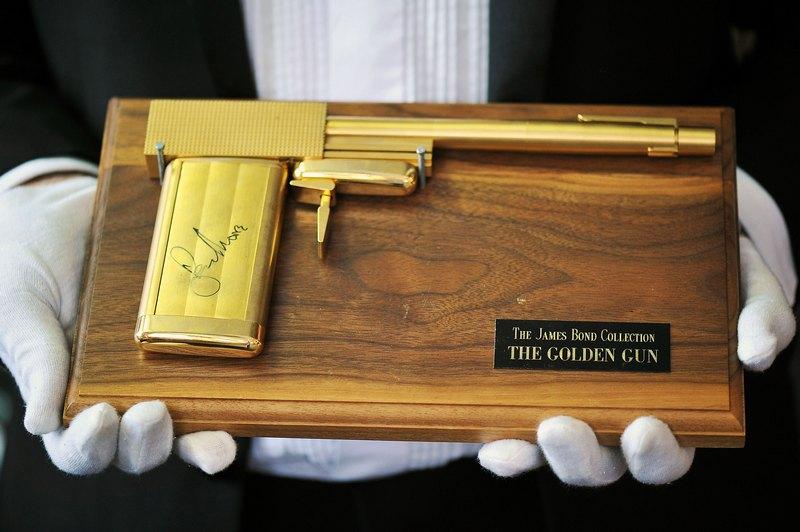 Лондон, Англия, 28 июня. Копия пистолета из фильма о Джеймсе Бонде 1974 года «Человек с золотым пистолетом» оценочной стоимостью 3—4 тыс. фунтов стерлингов выставлена на аукционе памятных вещей. Фото: Bethany Clarke/Getty Images