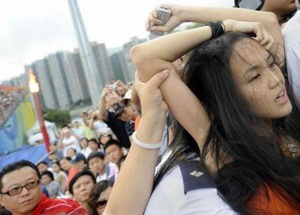 Поліцейські заарештовують дівчину, яка спробувала під час олімпійських змагань висловити протест проти придушення китайською компартією тибетців. 9 серпня. Гонконг. Фото: DAVID HECKER/AFP/Getty Images