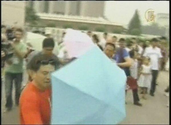 Полицейские в штатском раскрытыми зонтами заслоняют участников акции протеста от репортёров. 7 августа. Фото: кадры NTDTV