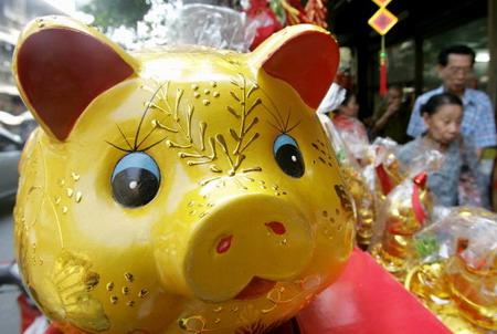 Таиланд, г.Бангкок: на шумных улицах продаются талисманы года: золотой поросенок. Фото: Pornchai Kittiwongsakul/AFP