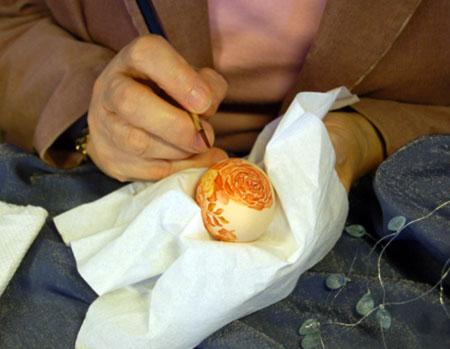Аренс Миа из Нидерландов расписывает яйцо акварельными красками. Фото: Великая Эпоха