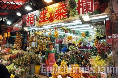 Прилавки для продуктов в магазине гонконгского района Дунмэнь в канун Нового Года превратились в прилавки для продажи новогодних цветов. Фото: Пан Цзинчао/Великая Эпоха
