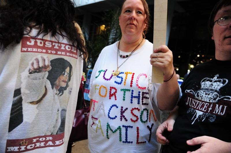Сторонники и противники Конрада Мюррея за пределами здания суда держат плакаты. Фото: Робин Бек / Getty Images