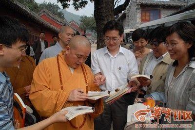 Настоятель монастыря Шаолинь Ши Юнсин даёт туристам на память автографы. Фото с сайта epochtimes.com