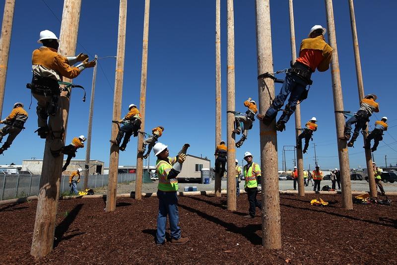 Окленд, США, 8 июня. Группа будущих электриков обучается навыкам лазания по столбам линий электропередачи. Фото: Justin Sullivan/Getty Images