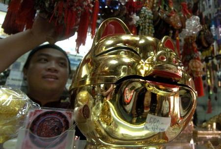 Филипины, г.Манила: торговец, который продает украшения для года свиньи. Фото: Joel Nito/AFP
